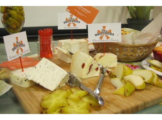 a display of different kinds of cheeses set out with pickles and pears, with the five brothers logo on signs attached to tooth pics stuck in the cheese