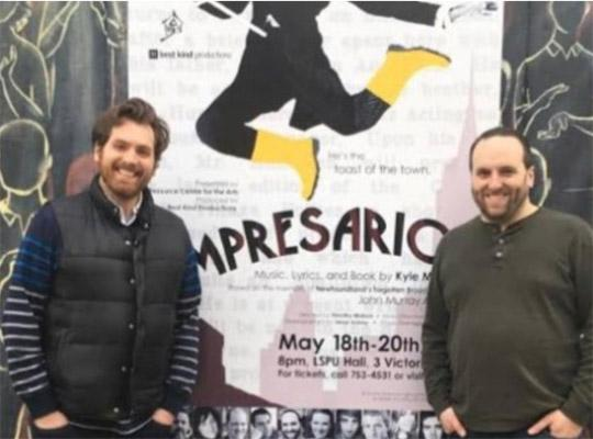 Kyle Mcdavid and Timothy Matson standing in front of a poster for their production of impresario