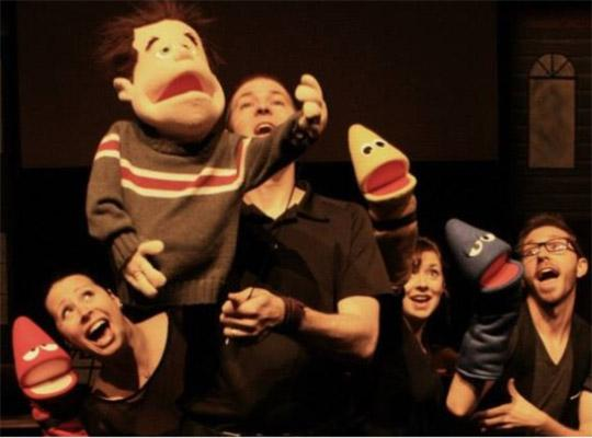 a group pf performers on stage with puppets