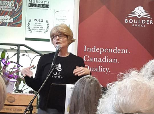 a woman gives a talk in front of a boulder books banner