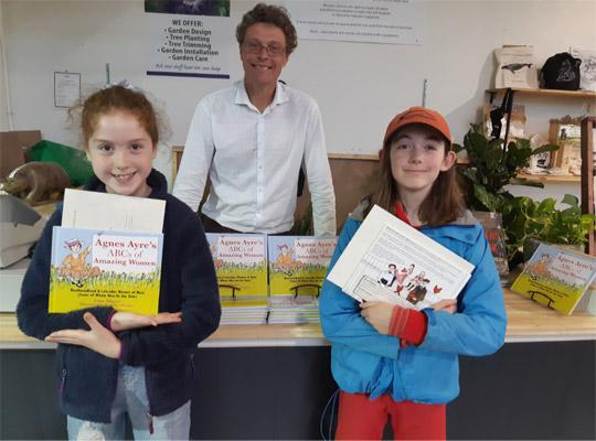 Gavin Will stands behind a book display. Two girls stand in front holding new books.