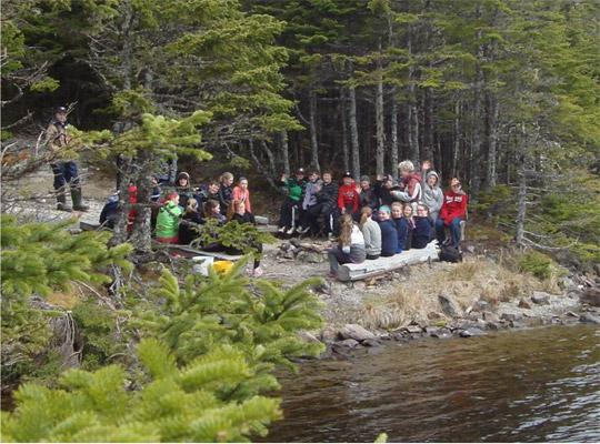 students standing by the waterside in the woods taking part in an activity
