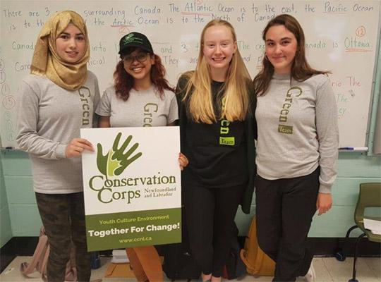 four young women holding a conservation corps sign and wearing Green Team sweaters