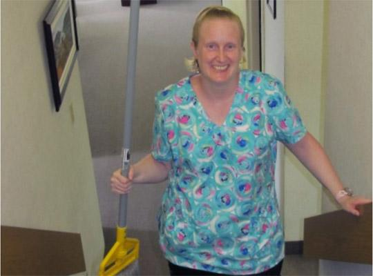 a woman wearing scrubs smiles holding a broom