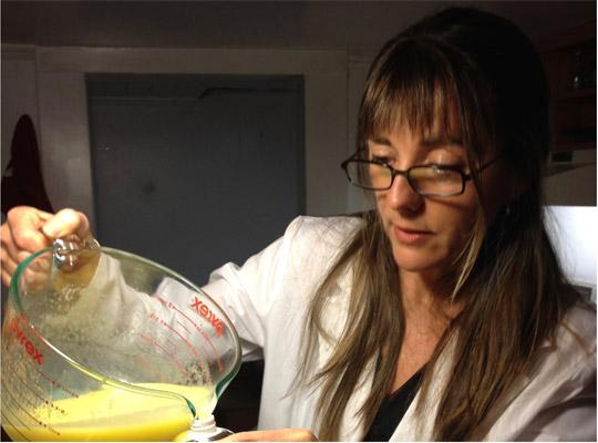 woman in lab coat pouring yellow liquid