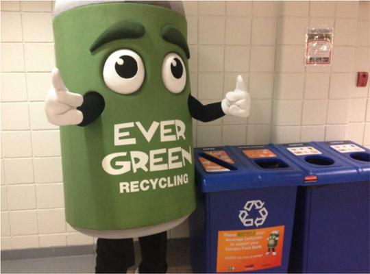 the Ever Green can mascot stands next to a recycling bin giving the thumbs up