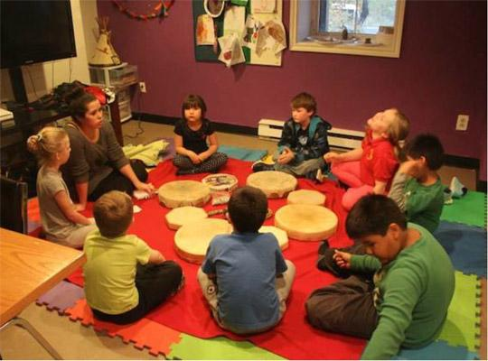 a group of children sitting in a circle with drums in the middle