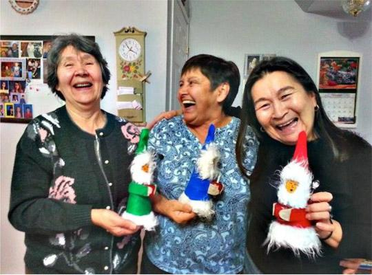 a group of people smiling and laughing holding hand made dolls