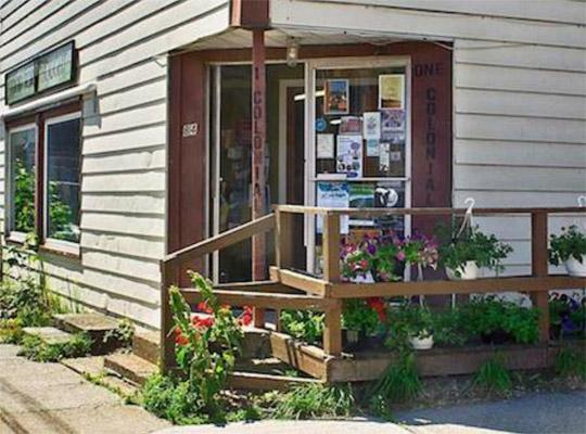 the outside of a store with plants covering the porch