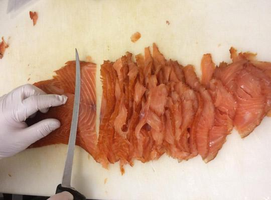 a gloved hand slicing smoked salmon with a knife