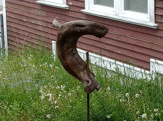 art that looks like a jumping whale of bronzed wood in a garden with grass and trees and a house in the background