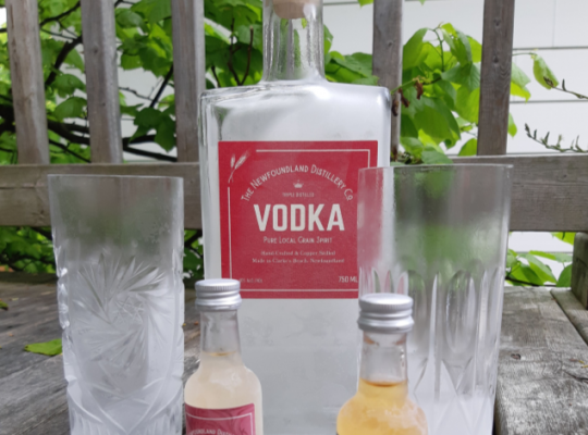 a bottle of Newfoundland vodka with two smaller bottles in front of it and glasses on either side of them