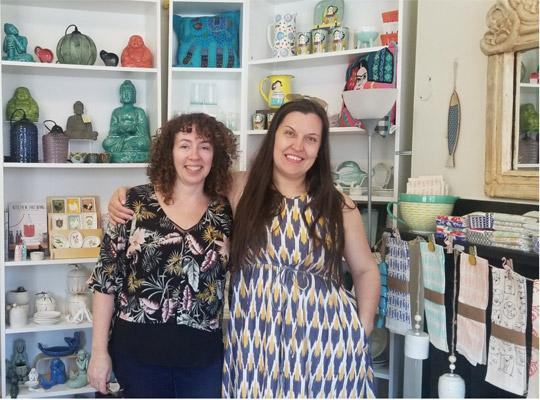 Jane and Anita pose in front of a shelf full of home decor