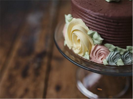 close up shot of the corner of a chocolate cake with icing roses piped onto the side
