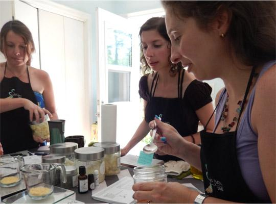 three women standing around a table making skincare products