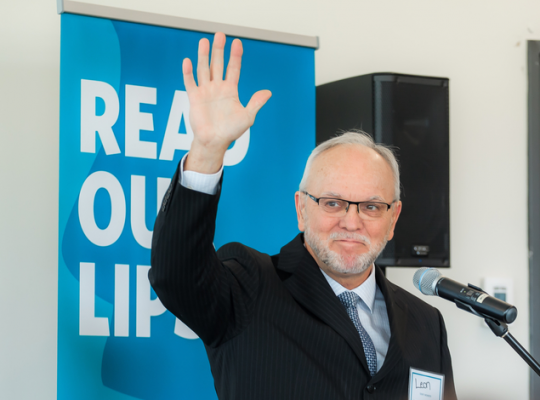 man at a microphone waving in front of a read our lips poster at the launching event