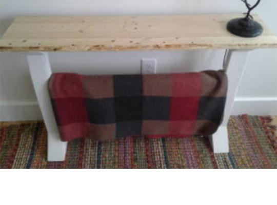long wooden table with a plaid blanket hung over the legs and a branch statue on top