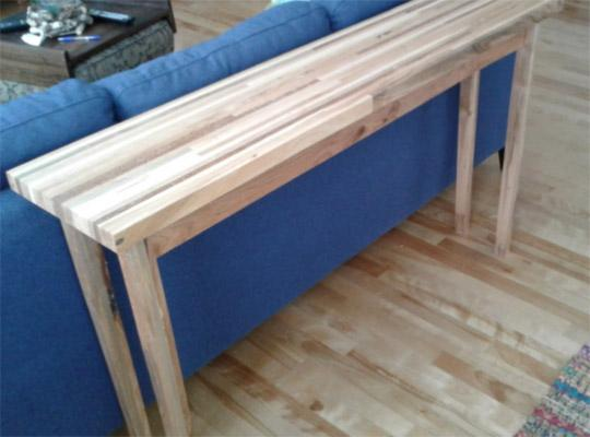 long wooden table in front of a blue couch