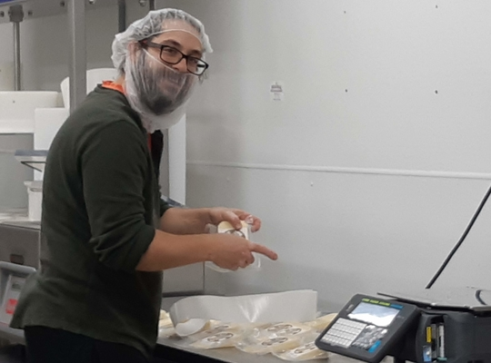 a happy young man wrapping cheese at Five Brothers Artisan Cheese, Goulds
