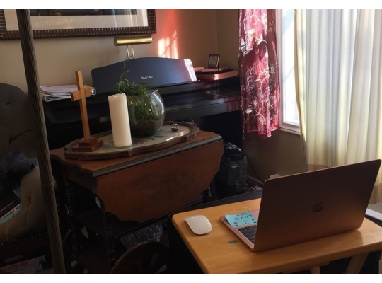 a cross, a candle, a plant and a laptop - everything Reverend Miriam Bowlby needs to bring Cochrane Street United Church's Sunday service live