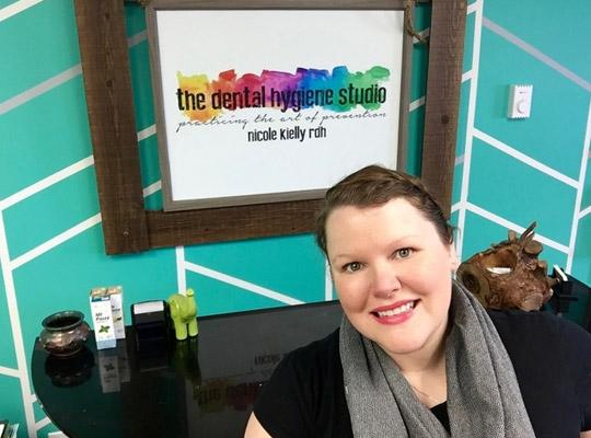 a woman smiling in front of a poster for the dental hygiene studio