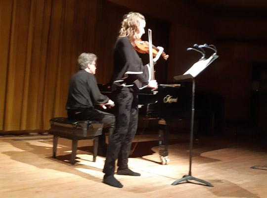 man playing piano and woman playing violin