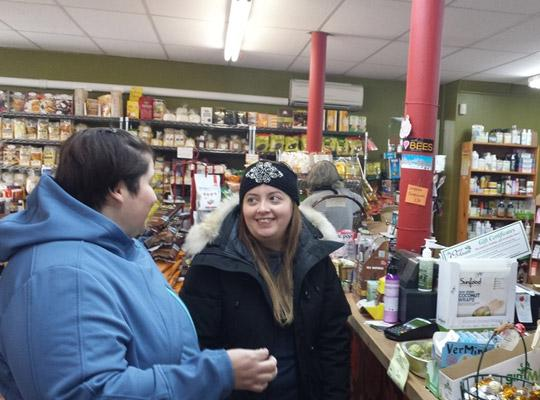 two happy customers chatting by the counter at Food for Thought healthy grocery