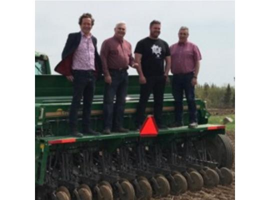 four men standing on top of a ploughing machine