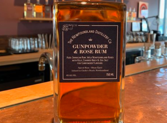 bottle of The Newfoundland Distillery Company Award-Winning Gunpowder & Rose Rum.  beautiful clear amber colour in rectangular rippled glass with a green label