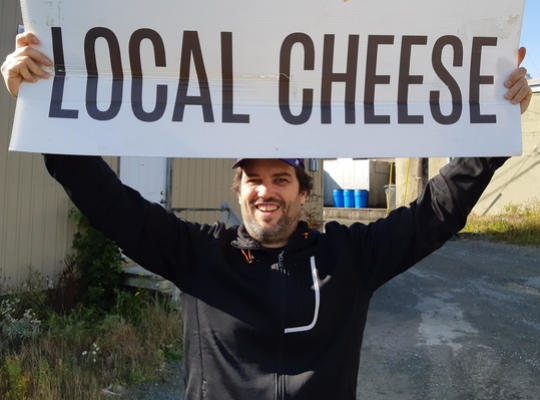 Adam Blanchard of Five Brothers Artisan smiling broadly and holding up a Local Cheese sign