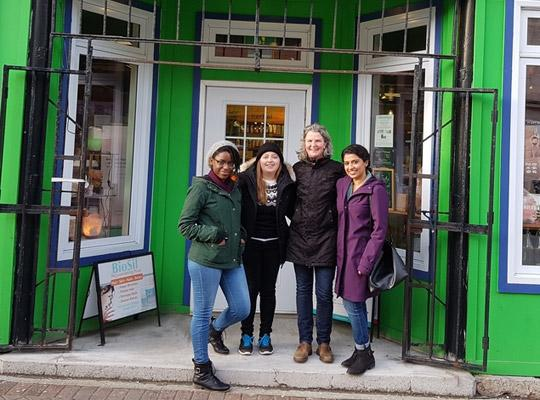 four women standing in front of the Natural Vibe shop on Water Street