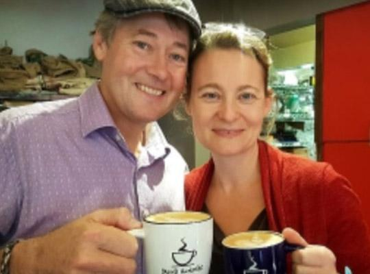 smiling man and woman holding mugs of coffee