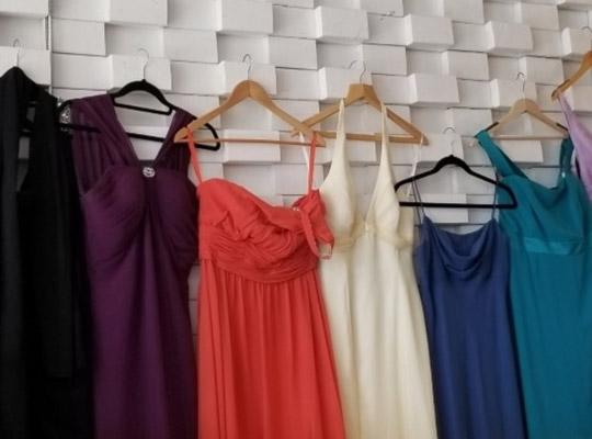 colourful prom dresses lined up on hangers