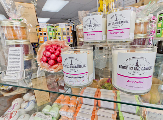 bright, clear display of products sold at the Heritage Shops - foggy island candles, row houses, and soap