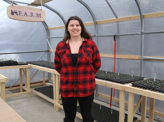 smiling dark-haired woman in a red shirt in a greenhouse surrounded by flats of seedlings