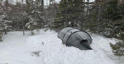 there is a large gray circular tent set up on a blanket of snow in the middle of a wooded area during the daylight
