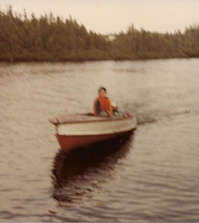 boy motoring a small wooden boat