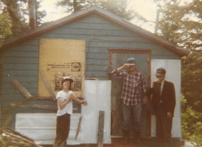 young boy and two men standing in front of a very rough looking cabin.  one of the men is wearing a sports coat