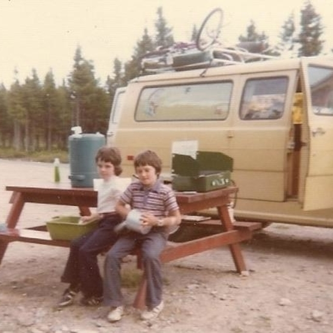 children on vacation in the 1970s, sitting at a picnic table doing dishes
