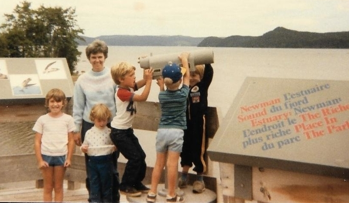 woman with five kids, three of whom are swinging a large telescope, standing in front of a fjord in Terra Nova National Park