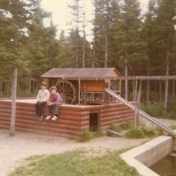 two children sitting in front of a replica waterwheel at a provincial park in Newfoundland