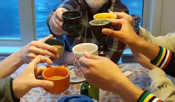 six hands holding six colourful mugs filled with tea.