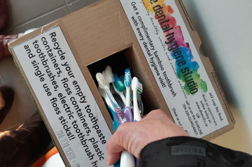 toothbrushes being put in a TerraCycle box for recycling put out by the dental hygiene studio